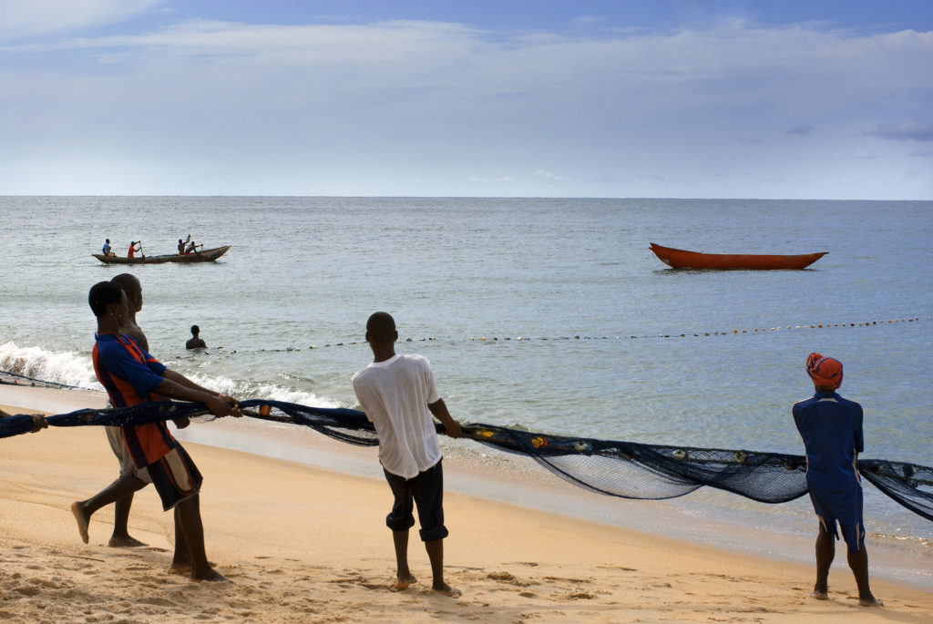 Fishermen pull a net from the ocean
